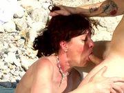 Une vielle qui suce un minet sur la plage